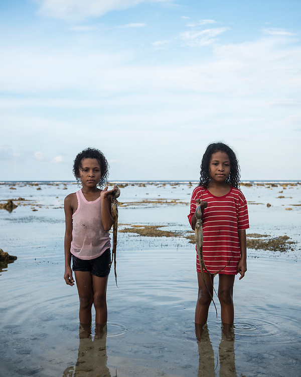 Jayapura, Papua, Indonesia - July 15, 2017: Jeklin, age 7, and Jesica, age 9, each holding a freshly caught octopus, stand in the shallow water at Pantai Base G, a beach on the outskirts of Jayapura, Papua, Indonesia. The family is from Biak, visiting Jayapura for vacation.