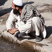 A man washing his hands in a gutter in the village of Nari, Kunar Province of Eastern Afghanistan.