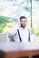 Businessman talking on mobile phone in outdoor cafe and drinking coffee, Munich, Bavaria, Germany