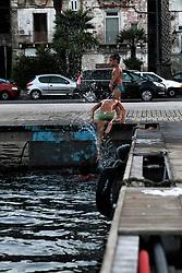 Bambini  nuotano nel porto della città vecchia di Taranto  tuffandosi dal pontile.