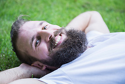 Happy young man lying in garden, Bavaria, Germany
