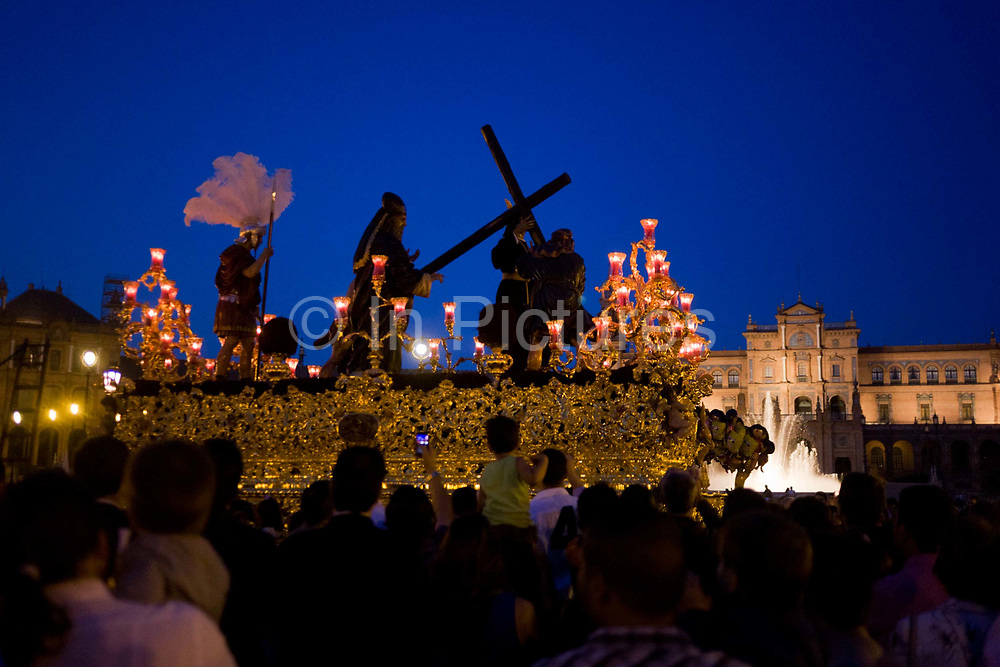 The Holy Paso depicting the Crucifixion passes through Seville's Plaza Espana during its annual Semana Santa Easter passion processions. Some 60 processions are scheduled for the week, from Palm Sunday through to Easter Sunday morning. The climax of the week is the night of Holy Thursday, when the most popular processions set out to arrive at the Cathedral on the dawn of Good Friday, known as the madrugá. At the centre of each procession are the pasos, an image or set of images set atop a movable float of wood. The structure of the paso is richly carved and decorated with fabric, flowers and candles. Many of the structures carrying the image of Christ are gilded, and those carrying the image of the virgin often silver-plated.
