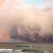 Isolated snow flurries off the coast of Wrightsville Beach North Carolina form an amazing display for a lone paddle boarder beneath them. Stand Up Paddle Boarding is a relatively new sport in which riders remain upright on a large board while using a custom oar to propel themselves into waves.