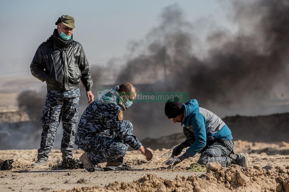 November 23, 2016 - Qayyara, Ninewa Province, IRAQ - Iraqi authorities carefully remove an unexploded mortar that was found close to the firefighting efforts. (Credit Image: © Gabriel Romero via ZUMA Wire)