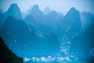 High angle view of a small village surrounded by blue Karst formations near Yangshuo, China.
