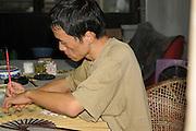 China, Zhejiang Province, Wuzhen local artist painting Chinese motifs on a fan
