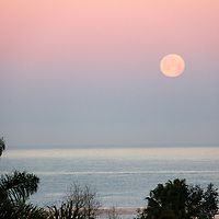 USA, California, San Diego. Full moon setting over the Pacific in the early morning.
