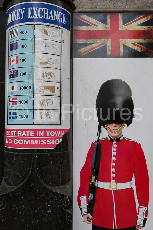 An image of a guardsman and a money exchange list that once displayed foreign currencies and their values, on 3rd February 2017, in London, England.