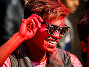 12 MARCH 2017 - BHAKTAPUR, NEPAL: A man with red powder on his face at a Holi celebration in Bhaktapur. Holi, a Hindu religious festival, has become popular with non-Hindus in many parts of South Asia, as well as people of other communities outside Asia. The festival signifies the victory of good over evil, the arrival of spring, end of winter, and for many a festive day to meet others. Holi celebrations in Nepal are not as wild as they are in India.     PHOTO BY JACK KURTZ