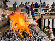"""11 SEPTEMBER 2015 - BANGKOK, THAILAND:  People burn """"ghost money"""" before a food distribution for poor members of the community at Wat Kalayanamit in the Thonburi section of Bangkok. Food distribution is a common way of making merit in Chinese Buddhist temples. Wat Kalayanamit, a Thai Theravada temple, was founded by a Chinese-Thai family in the 1820s and observes both Thai and Chinese Buddhist traditions. The food distribution was not related to the temple's efforts to evict people living on the temple grounds, but many of the people at the food distribution live in the houses the temple plans to raze.   PHOTO BY JACK KURTZ"""