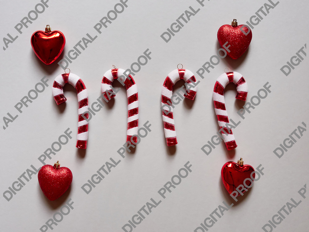 Christmas candy cane and hearts at studio above view over a grey cream background isolated flatlay