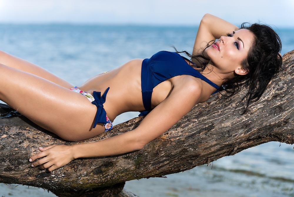 Beautiful shapely young woman in a bikini relaxing on a branch sunbathing in the sunshine overlooking a tropical beach and ocean