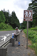 Humorous photograph of a detective standing next to a HIKERS trailhead sign looking at the road where the hiker silhouettes from the sign are splayed like chalk outlines of hit-and-run victims.