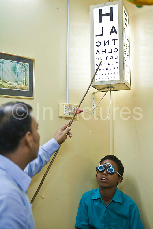 A young boy receives an eye examination from Dr Mohamed Shaheen on the IFB Jibon Tari Floating Hospital moored up on the banks of the Modhumoti River.  The Jibon Tari normally moves location every 3 months to remote riverine and offshore areas. It was launched in 1999 and has been major success, reaching more that 200,000 people.  <br /> Impact Foundation Bangladesh (IFB) provide care, support and treatment to people with disabilities in Bangladesh.