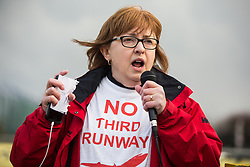 London, UK. 8 December, 2019. Christine Taylor of Stop Heathrow Expansion addresses climate activists from Extinction Rebellion outside Heathrow airport at a Bikes Against Bulldozers protest against Heathrow expansion and the greenwashing of climate commitments by political parties. The protest took the form of a Critical Mass bicycle ride from Hyde Park followed by a lie-in in front of a full-scale mock-up of a bulldozer to which Boris Johnson and John McDonnell were invited in order to fulfil their pledge of lying down in front of bulldozers to be used for Heathrow expansion.