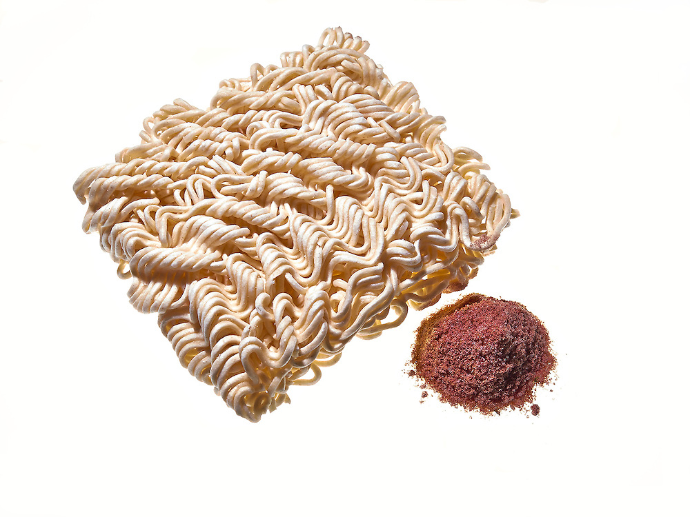 Dry ramen noodles on white .