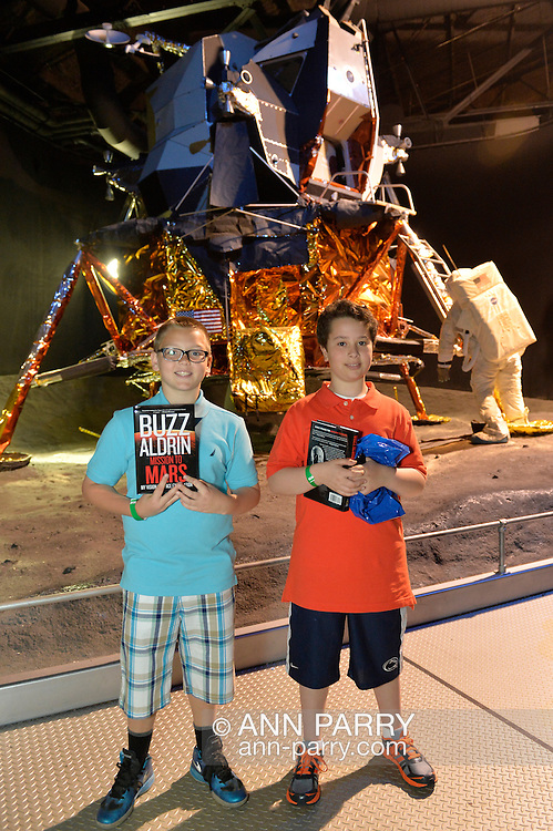 """May 11, 2013 - Garden City, New York U.S. -  Two smiling boys pose holding their copies of Buzz Aldrin's new book """"Mission to Mars"""" that the astronaut signed for them at the Cradle of Aviation Museum book signing, in front of LEM 13, the Grumman Lunar Module scheduled for Apollo 19, which was canceled."""