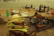 Corn roasted over charcoal and sold by the piece near the port in Alexandria, Egypt. The sky and light are orange due to a sandstorm. (Supporting image from the project Hungry Planet: What the World Eats.)