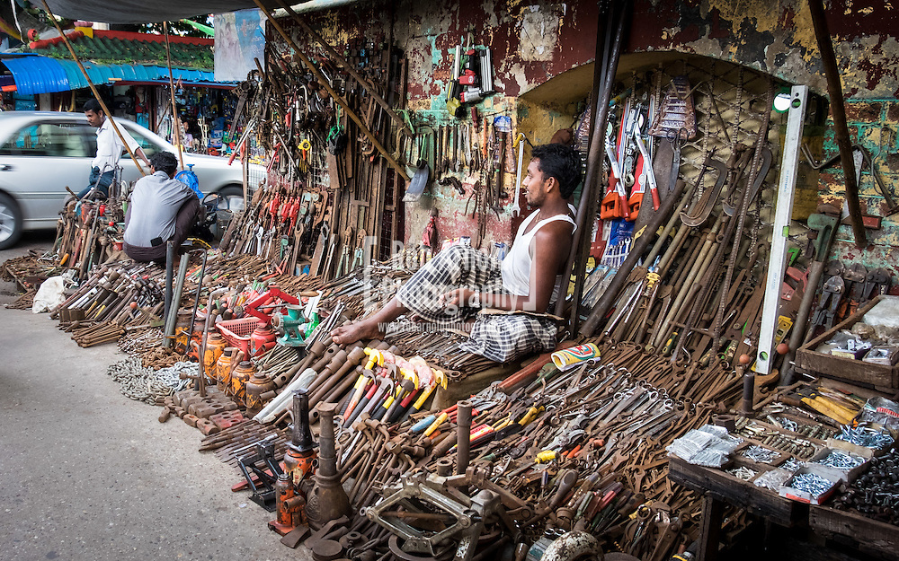 A man sitting on a pile of used tools at his street market stall in Yangon.