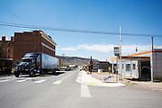 Een vrachtwagen passeert het eens fameuze Goldfield Hotel uit 1905 (links) en de Dahlstrom garage uit 1930. Goldfield, Nevada, is een bijna verlaten ghost town in Esmeralda County, gelegen aan de State Route 95. Tussen 1906 en 1910 was Goldfield de grootste plaats in de Amerikaanse staat Nevada met meer dan 20.000 inwoners. Momenteel leven er tussen de 200 en 300 mensen. Het plaatsje is groot geworden door de vondst van goud in 1902. Vanaf 1910 daalde het aantal inwoners snel en in 1923 is een groot deel verwoest door een brand. De overgebleven huizen zijn grotendeels verlaten, maar worden nog altijd onderhouden door de inwoners. Daarmee wordt de geschiedenis van de het plaatsje bewaard.<br /> <br /> A big tuck passes the once famous Goldfield Hotel of 1905 (left) and the Dahlstrom's Garage of 1930. Goldfield, Nevada, is an almost deserted ghost town in Esmeralda County. Between 1906 and 1910, Goldfield was the largest town in the state of Nevada with more than 20,000 inhabitants. Currently, there are between 200 and 300 people. The town has grown with the discovery of gold in 1902. From 1910, the population declined rapidly, and in 1923 the town was largely destroyed by a fire. The remaining houses are largely abandoned, but are still maintained by the residents. This way the history of the town is preserved.
