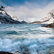 storm blows waves crashing down on the shore of saint mary's lake glacier national park, montana