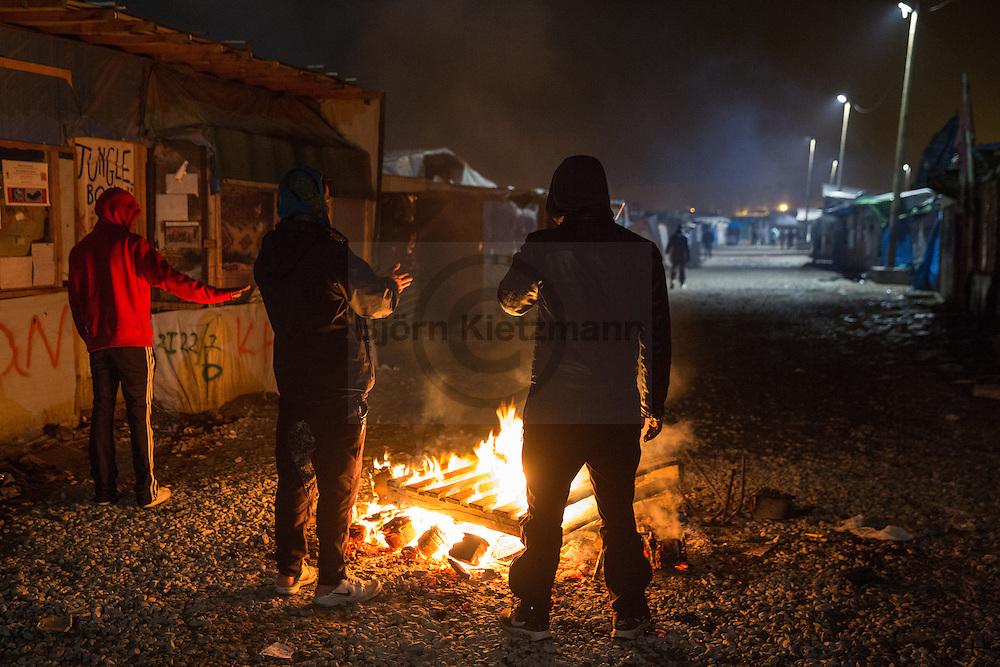 """Calais, Pas-de-Calais, France - 24.10.2016    <br />  <br /> Refugees warm on a fire. Start of the eviction on the so called """"Jungle"""" refugee camp on the outskirts of the French city of Calais. Refugees and migrants leaving the camp to get with buses to asylum facilities in the entire country. Many thousands of migrants and refugees are waiting in some cases for years in the port city in the hope of being able to cross the English Channel to Britain. French authorities announced a week ago that they will evict the camp where currently up to up to 10,000 people live.<br /> <br /> <br /> Fluechtlinge waermen sich an einem Feuer. Beginn der Raeumung des so genannte """"Jungle""""-Fluechtlingscamp in der französischen Hafenstadt Calais. Fluechtlinge und Migranten verlassen das Camp um mit Bussen zu unterschiedlichen Asyleinrichtungen gebracht zu werden. Viele tausend Migranten und Fluechtlinge harren teilweise seit Jahren in der Hafenstadt aus in der Hoffnung den Aermelkanal nach Großbritannien ueberqueren zu koennen. Die franzoesischen Behoerden kuendigten vor einigen Wochen an, dass sie das Camp, indem derzeit bis zu bis zu 10.000 Menschen leben raeumen werden. <br /> <br /> Photo: Bjoern Kietzmann"""