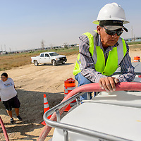 081915       Cable Hoover<br /> <br /> Milton Yazzie with the BIA fills tank for area rancher Melissa Badonie from a replacement tank at temporary water station south of Shiprock Wednesday.