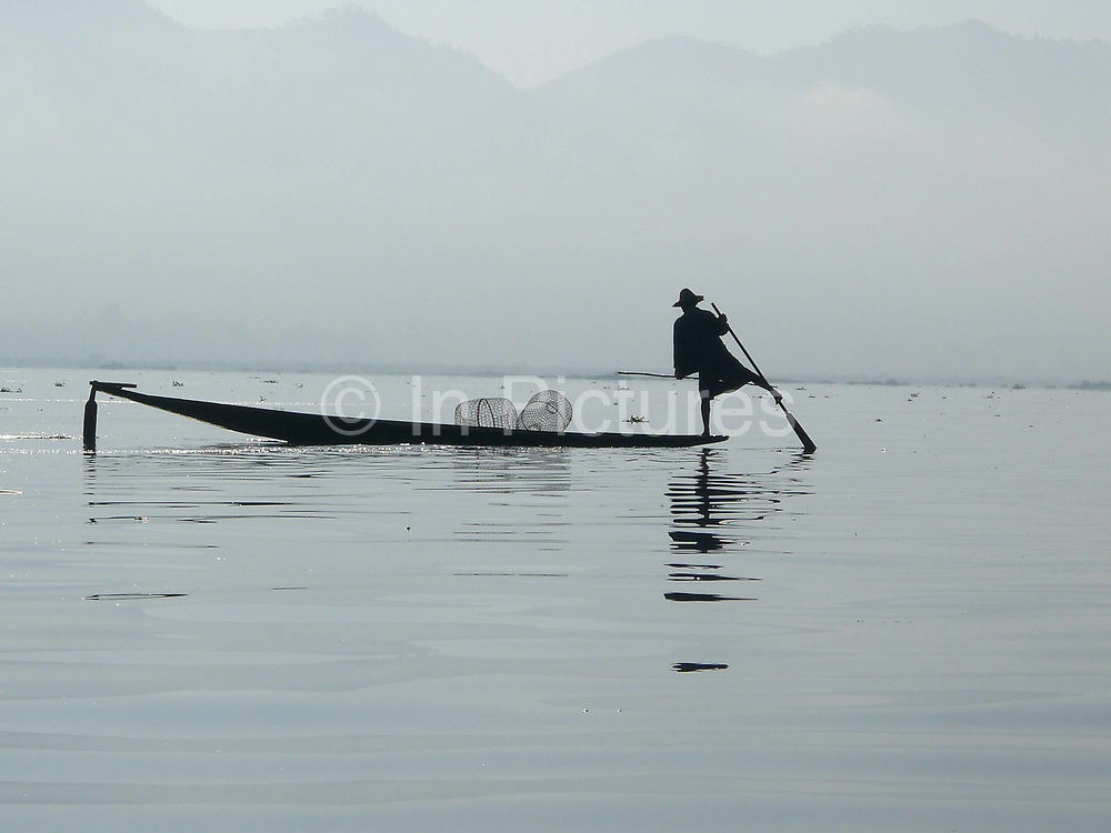 Intha fisherman fishing from a boat on Inle Lake on 4th January 2013 , Shan State, Myanmar.  Most Intha people get around on the lake using traditional flat-bottomed skiffs propelled by a single wooden paddle. The Intha technique of leg rowing - where one leg is wrapped around the paddle to drive the blade through the water is unique