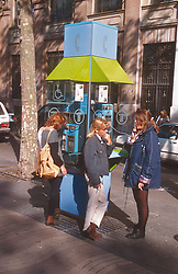 Teenagers standing in street using public phone box,
