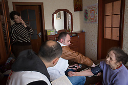 Lina (l) looks on as Doctor Khachatur Malakyan and nurse Andrei Bogma (c) look after her mother (r) in the small apartment they share with Lina's two young daughters and her husband. in Debaltsevo The family tries to care for Lydia, who suffers from Parkinson's disease, but due to the recent conflict and the Ukranian government's halting of pension payments to residents in the town they are unable to obtain the necessary drugs except from humanitarian donations.