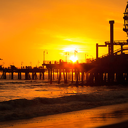 Santa Monica Pier sunset panorama photo with the Pacific Ocean in Los Angeles County Southern California. Santa Monica Pier is a landmark that has an amusement park with a ferris wheel, roller coaster, restaurants, and other attractions. Panoramic picture ratio is 1:3.