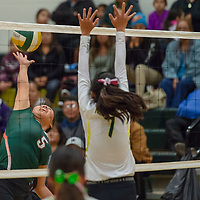 Wingate outside hitter Liyah Yazzie (5), strikes at the net for the Bears against a potential block by Hawks middle hitter Tatum Lee (7), in Thoreau Tuesday night.