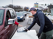 "11 APRIL 2020 - DES MOINES, IOWA: JORDON ELWELL, owner and CEO of Midwest Foods, uses a plastic table to pass a ready to cook pasta meal to a motorist during a food distribution in Des Moines. Most non-essential businesses in Iowa are closed until 30 April. Because of business closings causes by the Novel Coronavirus (SARS-CoV-2) pandemic, well over 100,000 Iowans filed first time claims for unemployment in the last three weeks, more than applied during the peak of the Great Recession of 2008. Local food banks have seen an unprecedented spike in people seeking nutritional assistance. Midwest Foods, a Des Moines based company and owner of Ginos Fine Italian Foods, gave away 1,000 complete dinners with sauce, noodles, salad, and dressing Saturday morning. People started lining up 3 hours before the food distribution began. The food distribution was done following ""social distancing"" guidelines and all of the workers wore masks and gloves.      PHOTO BY JACK KURTZ"