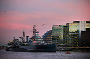 HMS Belfast on the River Thames as night falls and the sunset eases into the evening. HMS Belfast is one of the icons of the River Thames. Moored just along from the large office buildings at More London, HMS Belfast is a museum ship,  permanently moored in London on the River Thames. She was originally a Royal Navy light cruiser and served during the Second World War and Korean War.