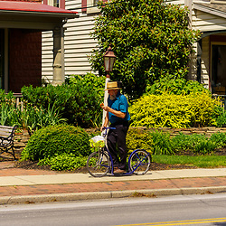 Intercourse, PA, USA / May 30, 2020: A Amish man enjoys a soft pretzel as he travels through the village on a bicycle scooter.