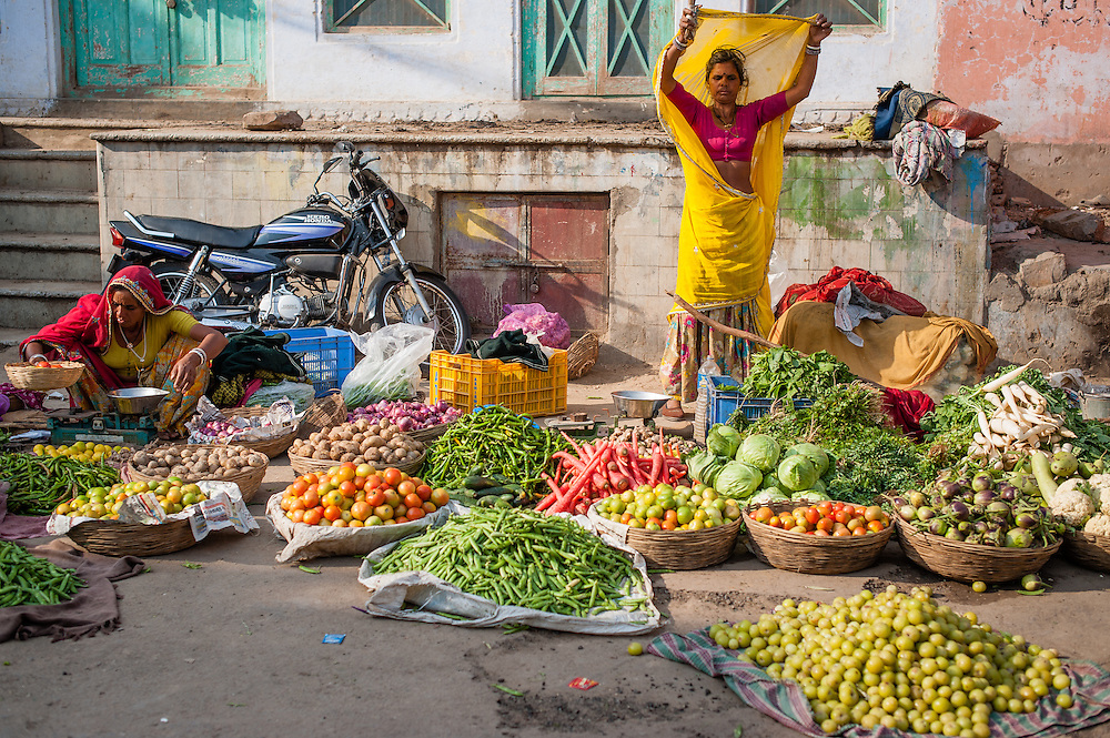 Woman selling vegetables at street market (India)
