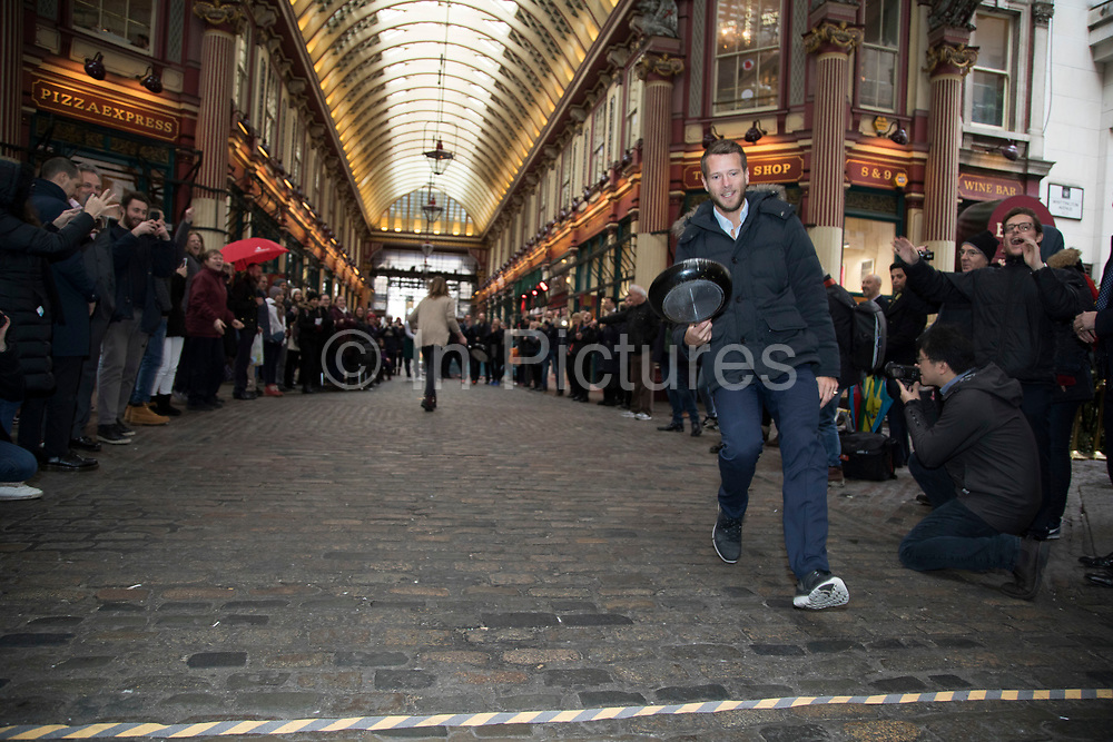 Shrove Tuesday festivities as competitors run the final of the Leadenhall Market Pancake Day Race on 13th February 2018 in London, United Kingdom. Competing teams of City workers outside The Lamb Tavern tackle the 25m course, competing to win the coveted frying pan trophy as they flip their wayaround the historic 14th century market.
