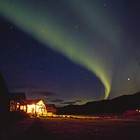 Yukon Territory, Canada. The aurora borealis sweeps across the sky above a lit up house.