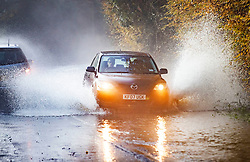 © Licensed to London News Pictures. 14/11/2019. Charlwood, UK.  Cars drive through flooding on a road near Charlwood in West Sussex. Environment Agency flood warning alerts are in place for homes near Ifield Brook and the River Mole neaby. Photo credit: Peter Macdiarmid/LNP