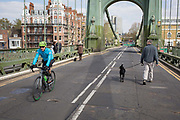 After being closed indefinitely to all traffic due to structural faults, a cyclist pedals over Hammersmith Bridge, on 11th April 2019, in west London, England. Safety checks revealed critical faults and Hammersmith and Fulham Council has said its ben left with no choice but to shut the bridge until refurbishment costs could be met. The government has said that between 2015 and 2021 its is providing £11bn of support to the 132-year-old bridge.