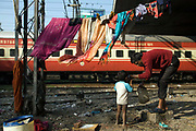 Vishal, a homeless man whose family lives by the railway tracks in Okhla, washes his young child as a train roars past, New Delhi, India
