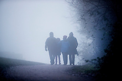 © Licensed to London News Pictures. 30/12/2016. Dorking, UK. A family walk on Box Hill on another day of fog and freezing temperatures. Photo credit: Peter Macdiarmid/LNP