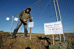 © Licensed to London News Pictures. 25/02/2012. Hinkley Point, Somerset, UK. Digging a waste pit. Anti-nuclear protesters are squatting on a disused farm on land where EDF Energy plans to build a new nuclear power station.  EDF is taking a case to the high court on Monday 27 February to evict the protesters and take out an injunction against all future protests at the site..Photo credit : Simon Chapman/LNP