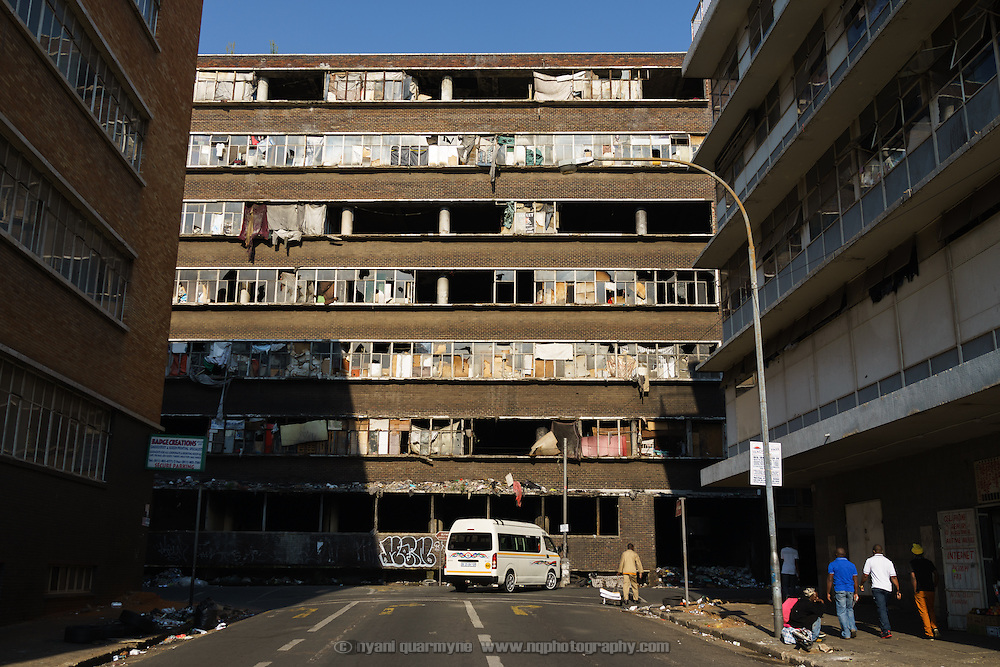 """A fire-damaged """"hijacked building"""" (illegally occupied squat) in downtown Johannesburg, South Africa. After a steep decline in the 1990s, the inner city is now a peculiar mix of interspersed working class, down-and-out and gentrified realities, all within a few minutes walk of each other."""