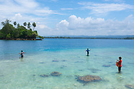 Three young ladies fish in the shallow water off Kranket Island in Madang, Papua New Guinea. They hand-hold the fishing line, use hermit crabs for bait, and put their catch in the plastic bags visible on their left arm.