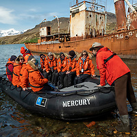 A Lindblad naturalist greets a zodiac filled with guests for exploration of the old whaling station at Grytviken on the north coast of South Georgia Island.