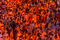 An entire hillside of people holding candles during a celebration of Meskel (an annual religious holiday of the Ethiopian Orthodox Church which commemorates the discovery of the True Cross by the Roman Empress Helena in the fourth century. Meskel includes the burning of a large bonfire, or Demera. Arba Minch, Ethiopia.
