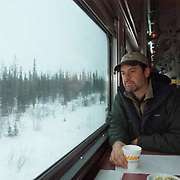 Daniel J. Cox takes a coffee break in the dining car of the CN Railroad heading to Churhill, Manitoba. Winter, frozen landscape with spruce forest passes by.