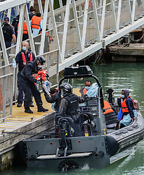 © Licensed to London News Pictures. 25/07/2021. Dover, UK. A young migrant is carried ashore by Border Force officers at Dover Harbour in Kent after crossing the English Channel. Hundreds of migrants have made the crossing in the calm weather this week. Photo credit: Stuart Brock/LNP