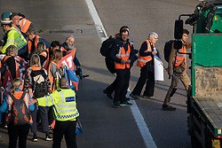 Ockham, UK. 21st September, 2021. Insulate Britain climate activists walk into the clockwise carriageway of the M25 between Junctions 9 and 10, some carrying power tools and other objects, as part of a campaign intended to push the UK government to make significant legislative change to start lowering emissions. Traffic was briefly halted on both carriageways of the motorway before the activists were removed and arrested by Surrey Police.